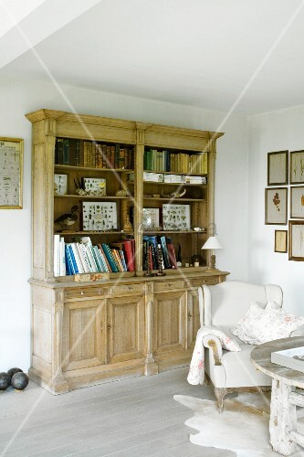 Collection of butterflies on rustic bookcase next to antique pale leather armchair