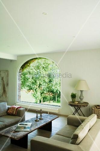 Gemütliche Lounge mit rustikalem Couchtisch und sommerlichem Gartenblick durch Rundbogenfenster