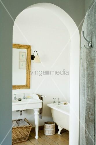 Blick durch Rundbogenöffnung in nostalgisches Badezimmer