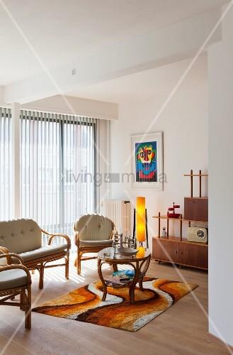 Wohnzimmer im Retrostil mit Rattanmöbeln und Musterteppich