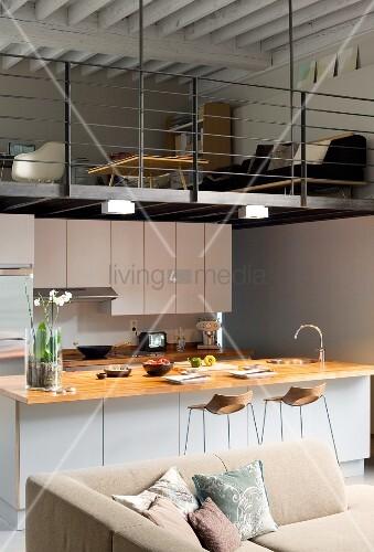 Kitchen below living room on mezzanine in open-plan interior