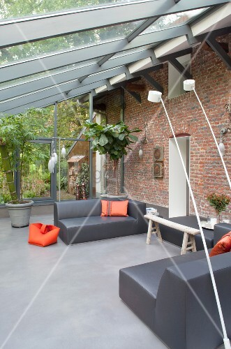 Grey designer lounge furniture and orange accents in conservatory extension on rustic brick façade