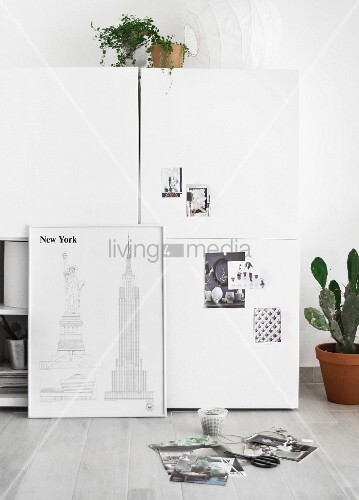 Sketches of New York leaning against white cabinet
