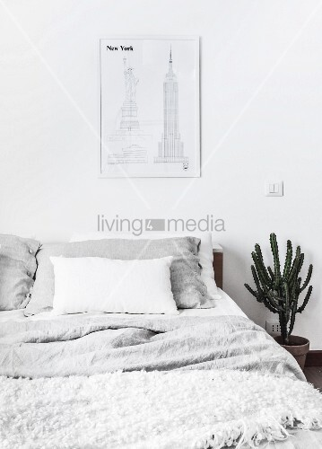 Sketches of New York above bed with pale bed linen