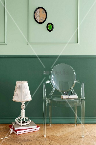 A green wall covering with decorative moulding and Biedermeier flair combined with a vintage table lamp next to a classic chair