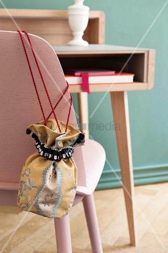A DIY fabric bag made of elegant Biedermeier fabric on a rose-coloured chair back