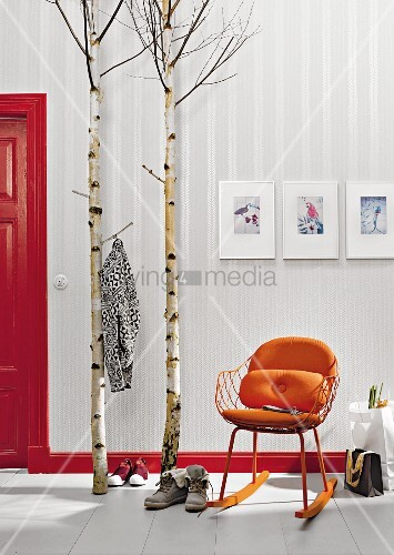 Birch trunks and stems used as a coat rack next to a an orange-coloured retro rocking chair in front of wallpaper with a shimmering fishbone pattern