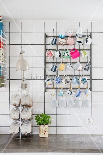 Various cups hung on rack mounted on white-tiled wall