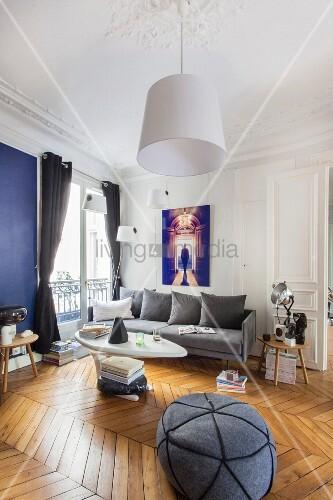 Retro living room with herringbone parquet floor in renovated period apartment