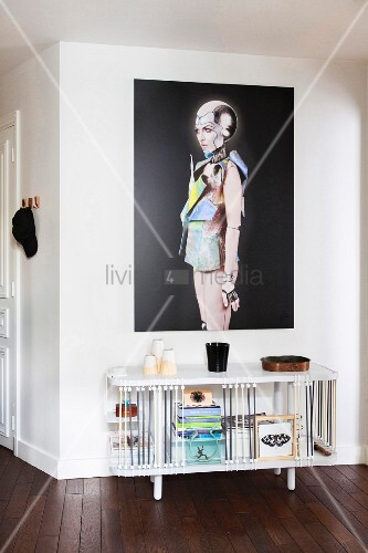 Modern picture of woman above white sideboard with expanders, stacked books and home accessories