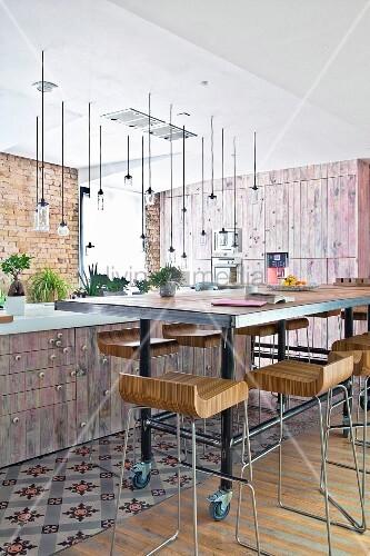 Designer-Barhocker vor langem Esstisch auf Rädern vor Kücheninsel