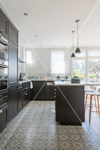 Black fitted kitchen with white worksurface and ornamental tiled floor