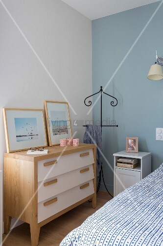 Valet stand between chest of drawers and bedside cabinet in corner of bedroom