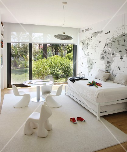 White, modern nursery with glass wall leading to garden