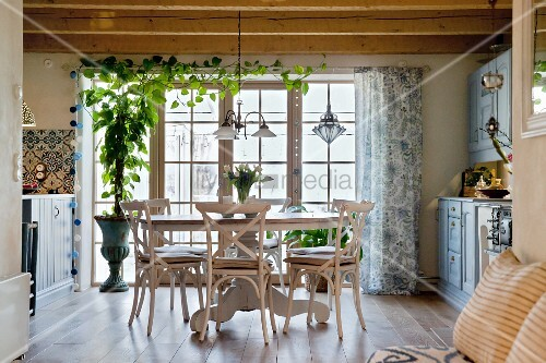 Cosy dining area with round table and rustic wood-beamed ceiling