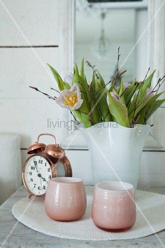 Pink tealight holders, alarm clock and tulips in white vase