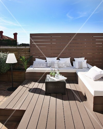 Elegant benches with white cushions and cushions on sunny roof terrace