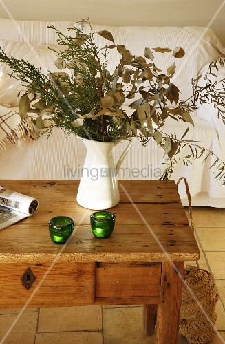 Jug of branches on wooden table in living room