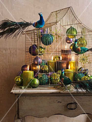 Baubles, candles and peacock figurines decorating bird cage