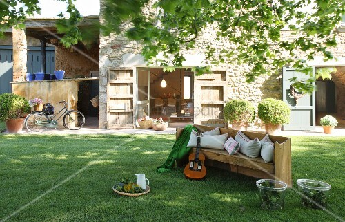 Guitar on wooden bench in garden outside stone house with open terrace doors