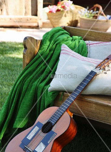 Guitar leaning against wooden bench with cushions and green blanket