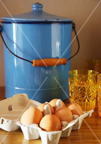 Eggs in egg boy in front of blue enamel bucket with lid