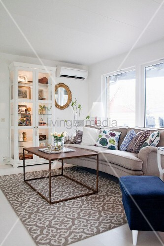 Cubic coffee table on patterned rug in front of sofa and display cabinet