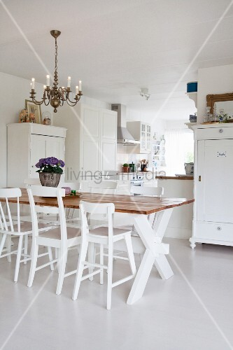 Various chairs around dining table in white open-plan interior