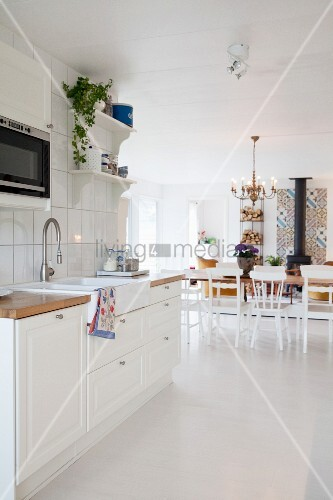 View from white kitchen into living area with dining table