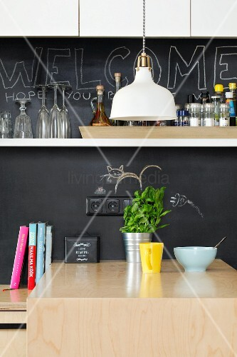 Kitchen counter with chalkboard splashback and white wall-mounted shelf
