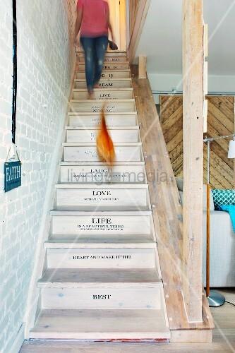 Restaurierte Holztreppe mit beschrifteten Stufen