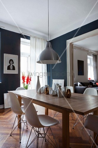 Wooden table in dining area of period apartment with dark grey walls