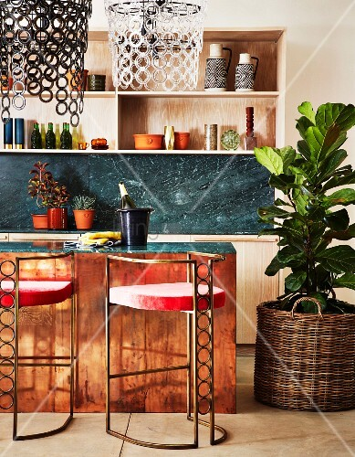 Art-Deco bar stools at kitchen counter and large house plant in basket