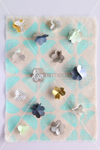 Small paper flowers on printed hand-made paper
