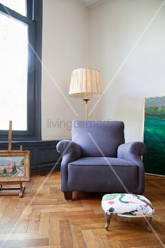 Blue armchair and retro standard lamp on oak parquet floor in period apartment