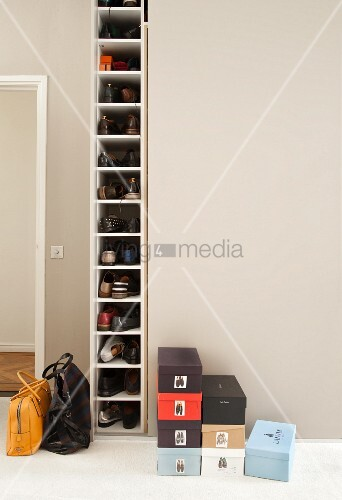 Many shoes in tall, narrow shoe cabinet next to stacked shoeboxes
