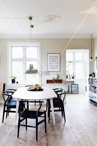 Black designer chairs around oval table in bright dining room