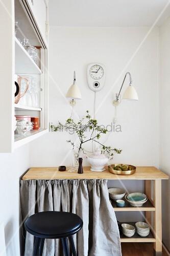 Holztisch mit Regalböden für Geschirr und hellgrauem Vorhang, darüber Wandleuchten und Retro Wanduhr