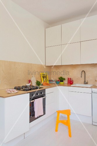 White fitted kitchen with wall units and splashback made from wooden panels