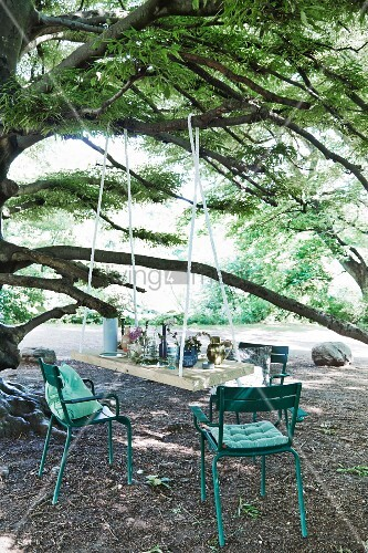 DIY table top suspended from tree and turquoise garden chairs