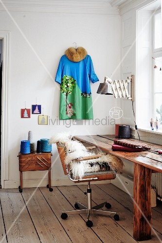 Rustic wooden table, sheepskin on retro office chair next to reels of thread on sewing box below dress hung on wall
