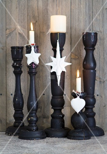 Christmas-tree baubles dipped in plaster and hung from black candlesticks