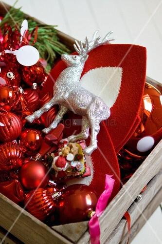 Holzkiste mit Deko-Hirsch und rotem Weihnachtsschmuck