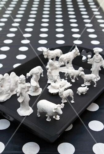 In Gips getauchte Krippenfiguren auf einem schwarzen Tablett