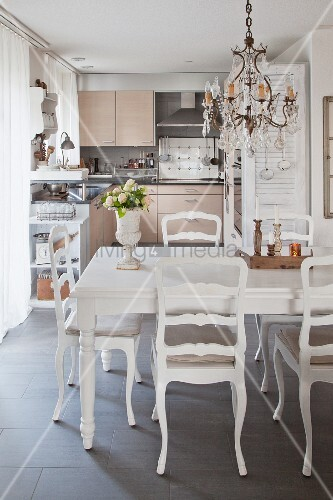 Dining table in front of open-plan, vintage-style kitchen