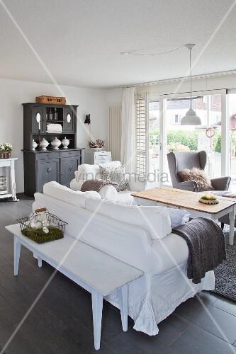 Alte Holzbank hinter dem Sofa im grau-weißen Wohnzimmer