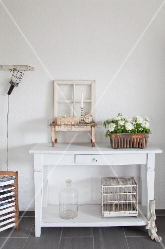 Altes Fenster, Vogelkäfig und Blumen auf weißem Konsolentisch