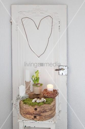 Naturdeko auf einem Holzblock vor einer alten Tür mit Drahtherz