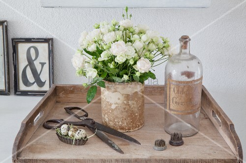 Vase of white roses next to old bottle and vintage ornaments