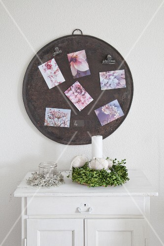 Rundes Blech als Magnetwand mit Postkarten überm Buchskranz